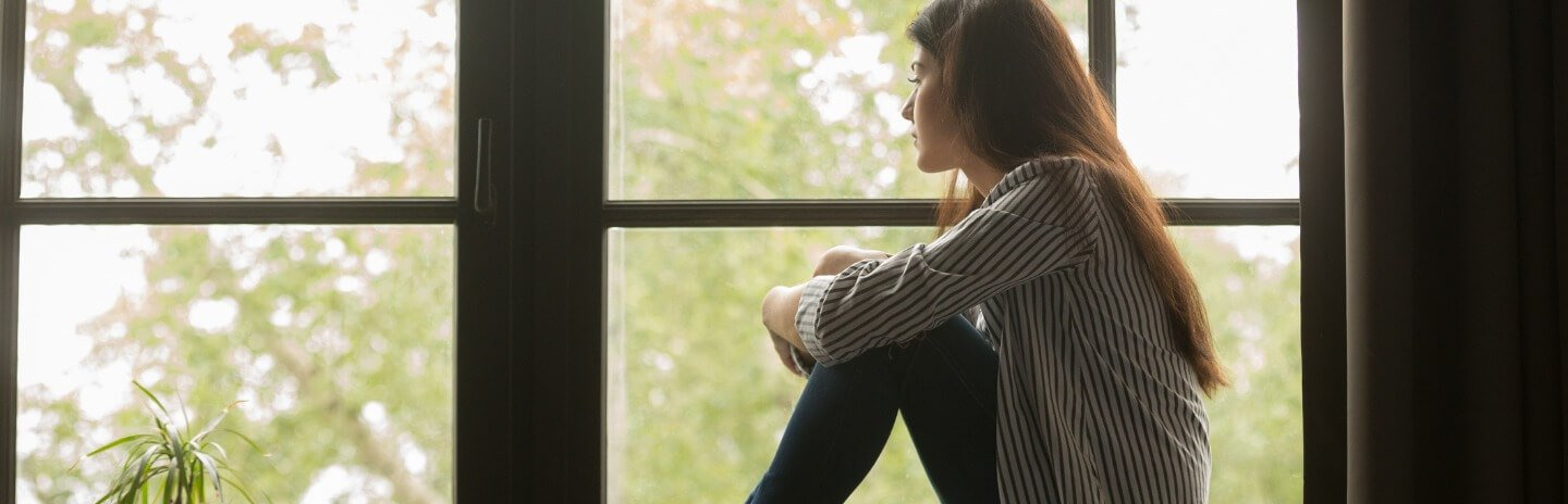 Girl sitting on sill looking out of window