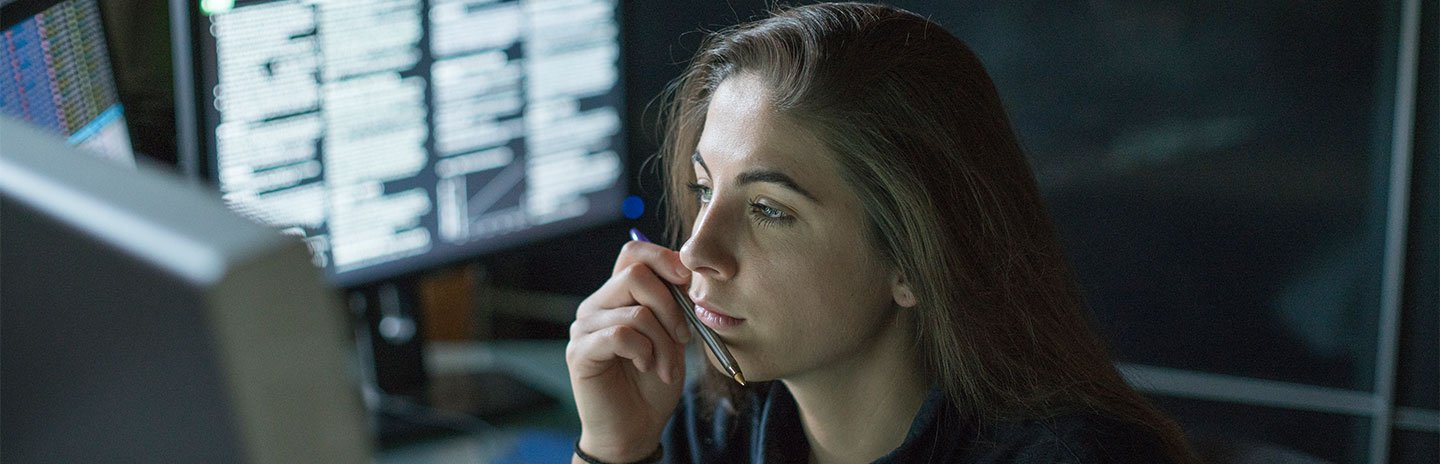 Girl in dark office looking at data