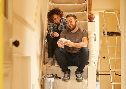 Couple sit on stairs checking out paint options for wall
