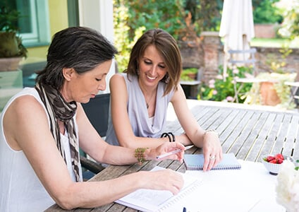 Mother and daughter sit at garden table planning future